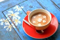 Roter Tasse Kaffee mit Herzen und Blume gemalt auf Schaum Lizenzfreies Stockfoto