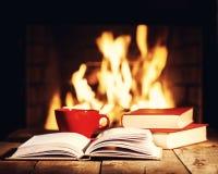 Roter Tasse Kaffee oder Tee und alte Bücher auf Holztisch nahe Tanne Lizenzfreie Stockfotografie