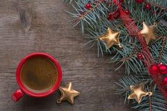 Roter Tasse Kaffee und Tannenzweig mit Weihnachtsdekorationen auf altem hölzernem Hintergrund Lizenzfreies Stockbild