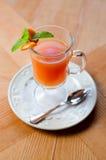 Roter Tee der Frucht mit Orange in der Glasschale, auf Holztisch Stockbild