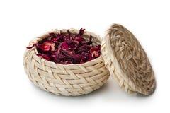 Roter Tee im Weidenkorb, lokalisiert auf weißem Hintergrund Stockfotos