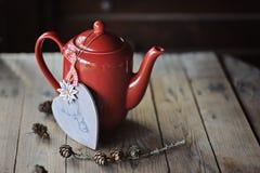 Roter Teetopf, Weihnachtsherz formte Dekorations- und Kiefernkegel Lizenzfreie Stockfotos