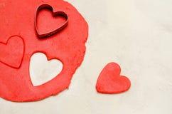Roter Teig mit einer Form, zum von Herzen auf einer weißen Tabelle, Raum zu schneiden und herauszuschneiden für Text lizenzfreie stockbilder