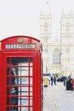 Roter Telefonkasten in London- und Westminster-Kathedrale im backgro Lizenzfreie Stockfotos