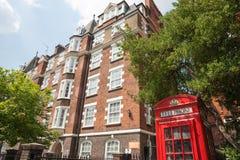 Roter Telefonkasten vor Wohnungen des roten Backsteins. Lizenzfreie Stockfotografie