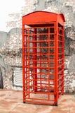 Roter Telefonzelle-Frontbacksteinmauerblock lizenzfreie stockfotografie