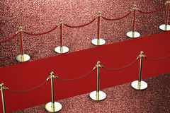 Roter Teppich mit Seilsperre auf rotem Hintergrund Stockfotografie