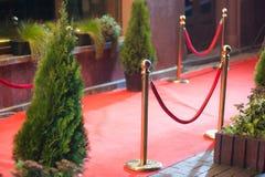 Roter Teppich - wird traditionsgemäß benutzt, um den Weg zu markieren, der durch Staatsoberhäupter bei den zeremoniellen und form lizenzfreies stockfoto