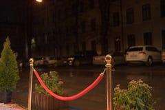 Roter Teppich - wird traditionsgemäß benutzt, um den Weg zu markieren, der durch Staatsoberhäupter bei den zeremoniellen und form stockbild