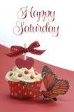 Roter Themakleiner kuchen mit Schmetterling auf rotem und weißem Hintergrund mit glücklichem Samstag-Beispieltext Stockfotografie