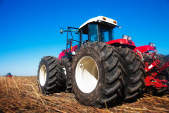 Roter Traktor auf dem Gebiet Stockbild