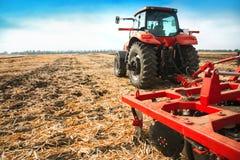 Roter Traktor auf dem Gebiet an einem hellen sonnigen Tag Stockbilder