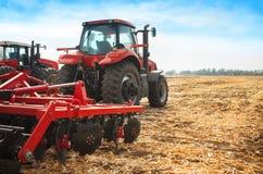 Roter Traktor auf dem Gebiet an einem hellen sonnigen Tag Stockbild