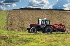 Roter Traktor auf dem Gebiet Landwirtschaftliche Bauernhofarbeit Landwirtschaft in der Tschechischen Republik Stockfotografie