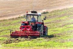 Roter Traktor auf dem Gebiet Landwirtschaftliche Bauernhofarbeit Landwirtschaft in der Tschechischen Republik Lizenzfreie Stockfotografie