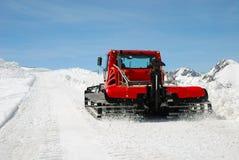 Roter Traktor auf Schneesteigung Stockfotografie