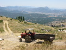 Roter Traktor mit dem Anhänger, der entlang ländliche Stadtrände fährt stockfotografie