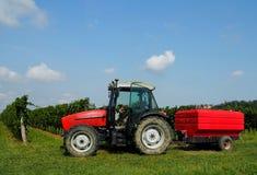 Roter Traktor mit der Tür offen und ein roter Anhänger vor Weinbergen unter blauem Himmel mit Wolken Stockbild