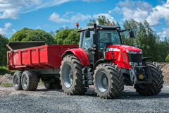 Roter Traktor mit einem Anhänger Stockbild