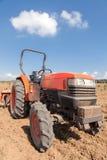 Roter Traktor mit Pflug auf dem Gebiet Bewölkter Himmel Lizenzfreie Stockfotografie