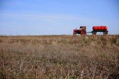 Roter Traktor mit Wasserbecken Lizenzfreies Stockfoto