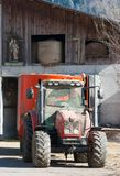 Roter Traktor und religiöse Statue in einem Bauernhof lizenzfreie stockbilder