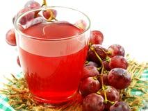 Roter Traubensaft mit der Frucht lokalisiert auf weißem Hintergrund Stockbild