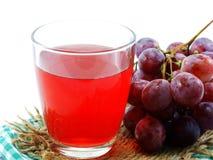 Roter Traubensaft mit der Frucht lokalisiert auf weißem Hintergrund Lizenzfreies Stockbild