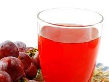 Roter Traubensaft mit der Frucht lokalisiert auf weißem Hintergrund Stockfotografie