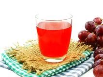 Roter Traubensaft mit Frucht auf weißem Hintergrund Lizenzfreie Stockbilder