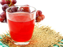 Roter Traubensaft mit Frucht auf weißem Hintergrund Lizenzfreies Stockfoto