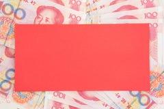 Roter Umschlag auf chinesischem Geldhintergrund Stockfotografie