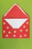 Roter Umschlag auf grünem Hintergrund, christmastime Lizenzfreie Stockbilder