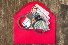 Roter Umschlag mit Eurorechnungen und den Handschellen Stockbilder