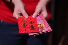 Roter Umschlag mit Segenwörtern für die Geschenke des Chinesischen Neujahrsfests in der Hand gehalten Stockfoto