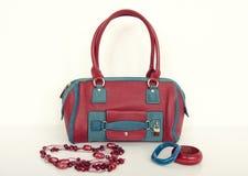 Roter und blauer Geldbeutel mit zusammenpassender Halskette und Armbändern Stockfotos