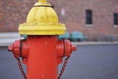 Roter und gelber Feuerhydrant mit Ziegelsteinhintergrund Lizenzfreies Stockfoto