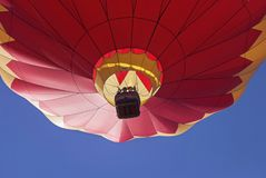 Roter und gelber Heißluft-Ballon gegen einen blauen Himmel lizenzfreies stockfoto