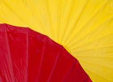 Roter und gelber Papierregenschirm Lizenzfreie Stockbilder