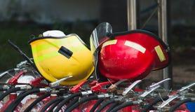 Roter und gelber Schutzhelm auf Feuerbehälter lizenzfreie stockfotos