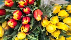 Rote und gelbe Tulpeblumensträuße am Markt. Stockbild