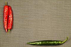 Roter und grüner heißer Pfeffer auf einem beige Hintergrund Stockfoto