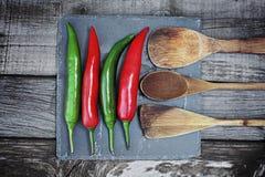 Roter und grüner Pfeffer des scharfen Paprikas auf hölzernem Hintergrund Lizenzfreies Stockbild