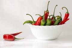 Roter und grüner Pfeffer des scharfen Paprikas in einer keramischen Schüssel Stockfoto