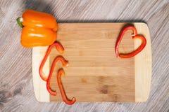 Roter und orange Paprika auf Schneidebrett Roter Pfeffer streift Whitholzhintergrund ab Stockfotografie