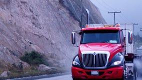 Roter und schwarzer LKW auf dem Regen stockfotos