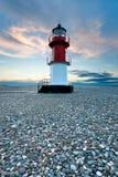 Roter und weißer Leuchtturm auf einem Strand mit Kieseln Stockfotografie