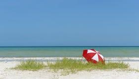 Roter und weißer Regenschirm auf Strand Stockfotografie
