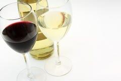 Roter und weißer Wein in zwei Gläsern mit einer Flasche Stockbild