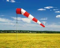 roter und weißer Windsock auf blauem Himmel auf dem Flughafen, dem gelben Feld und dem Wolkenhintergrund stockbild
